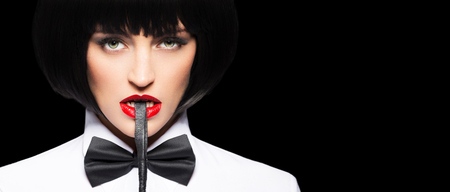 Sexy dominant woman in wig bite whip banner, isolated on black, bdsm