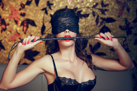 Sexy woman in blindfold bite whip with red lips, lace eye cover, bdsm 免版税图像