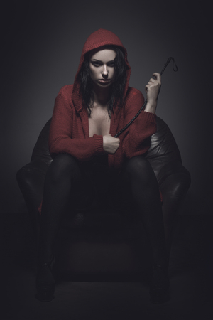 Little red riding hood with whip sitting on sofa in dark