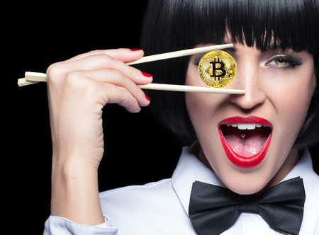 Young woman in bow tie and wig holding gold bitcoin coin by chopsticks in front of eye, isolated on black