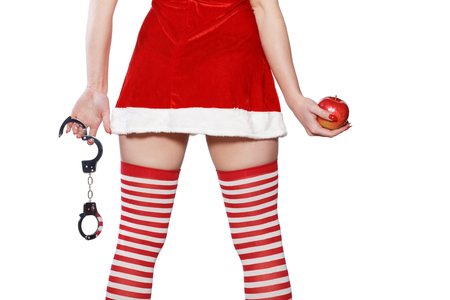 Santa woman holding red apple and handcuffs closeup, bdsm, isolated on white background