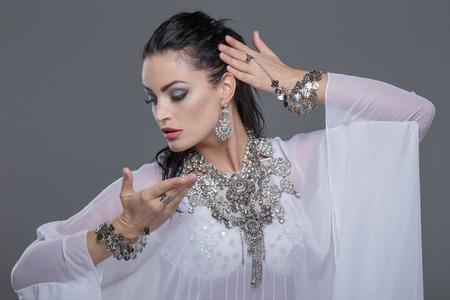 Beautiful oriental belly daner dancing on grey background, portrait Stock Photo