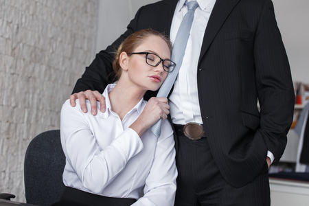 Young sensual businesswoman holding boss by necktie in office, lovers Stockfoto