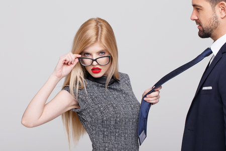 Sexy blonde manipulator woman pulling man by tie, holding eyeglasses Stock Photo