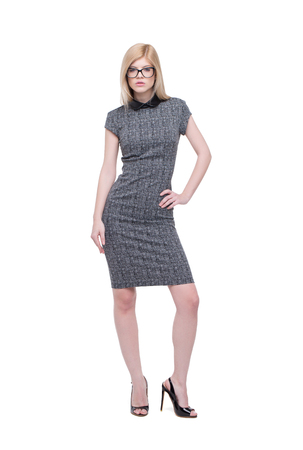 Young smart businesswoman in gray dress posing isolated on white