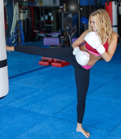 Young blonde kickboxer woman kick into heavy bag in gym
