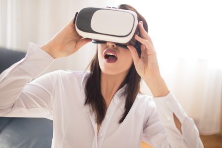 Young brunette caucasian woman in VR glasses amazed by concent 版權商用圖片