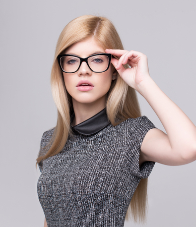 Young smart blonde casual woman holding eyeglasses on gray background