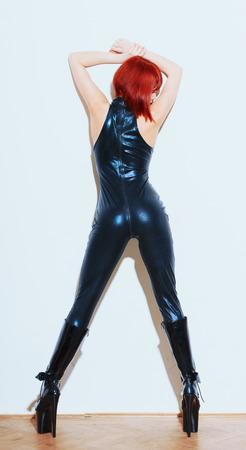 ラテックスキャットスーツのセクシーな赤毛のドミナトリクスと、壁に赤い髪をポーズしたハイヒールのプラットフォームブーツ