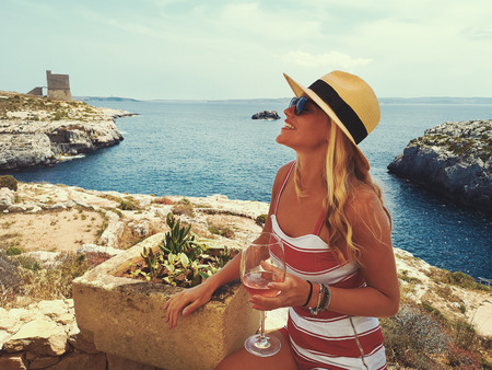 Young blonde woman in hat with drink enjoying the mediterranean feeling at seashore