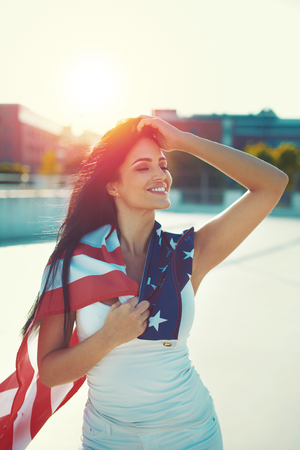Young woman covered USA flag daydreaming in sunset outdoors Stock Photo - 103363859