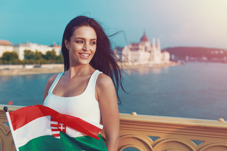 Young brunette woman holding Hungarian flag at Budapest, Danube river, Parliament building in background.