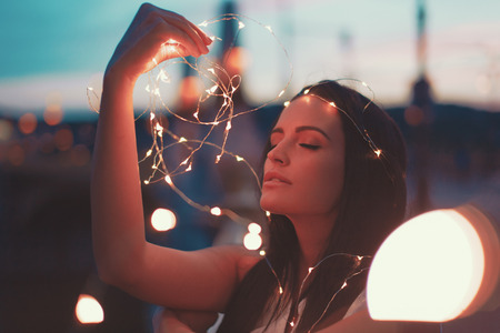 Sensual young woman playing with fairy lights outdoors, eyes closed, teal and orange style