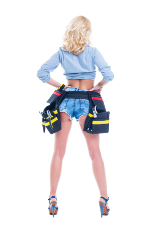 Sexy blonde woman in denim short and tool belt rear view, isolated on white Stockfoto