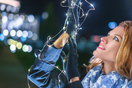 Young woman holding christmas fairy lights at night outdoors in city closeup