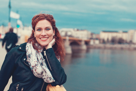Happy young redhead carefree woman toothy smile on Margaret bridge in cold weather, Budapest, Hungary 免版税图像
