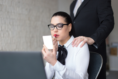 Married boss cheating with secretary concept, hand on her shoulder in office