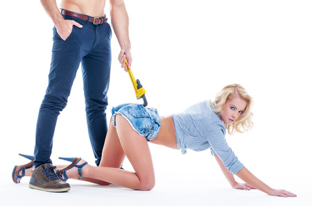 Naked plumber man in denim holding sexy woman by wrench on white background