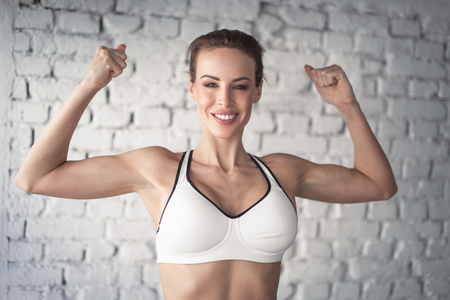 Young strong fit woman showing bicepses portrait in gym