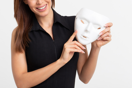 Happy young woman holding white mask on white background Imagens