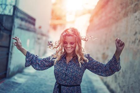 Happy joyful carefree woman dancing on moody narrow street in sunset Imagens