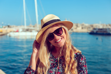 Young blonde mediterranean woman in hat portrait with toothy smile