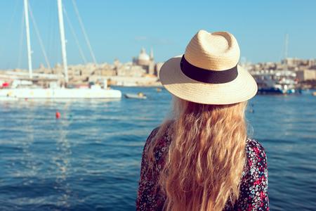 Mediterranean woman in enjoying Valletta panorama, Malta, rear view