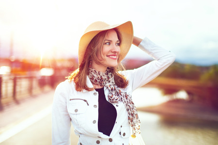 Modern positive woman in hat smiling in city sunset, outdoors