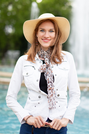 Happy young woman in hat smiling at fountain in park
