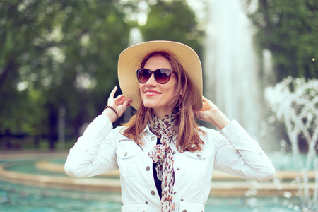 Happy young stylish woman in sunglasses holding hat in park with fountain, vintage style Фото со стока