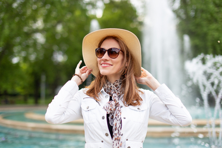 Happy young stylish woman in sunglasses holding hat in park with fountain Фото со стока