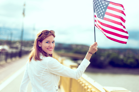 Young woman holding USA flag in town, selective focus, depth of field Фото со стока