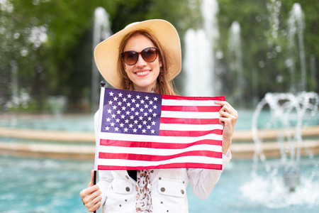 Happy young woman in sunglasses holding USA flag in park at fountains