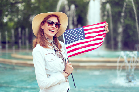 Young fashionable excited woman holding USA flag in park at fountain, Independece day, Fourth of July Фото со стока