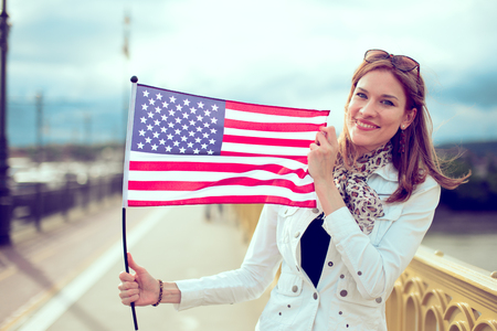 Young urban woman holding USA flag outdoors, 4th of July, Independence day
