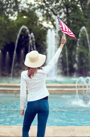 Patriot woman in hat holding USA flag in park rear view, Independence day, 4th of July Фото со стока