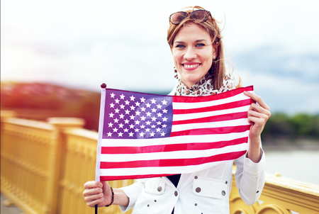 Happy young patriot american urban woman with toothy smile stretching USA flag Фото со стока