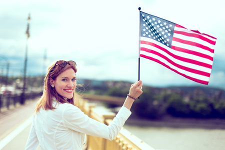 Happy young patriot modern urban woman holding USA flag portrait