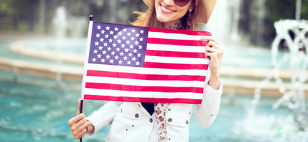 Happy young patriot woman in hat stretching USA flag in park concept, 4th of July, Indendence day