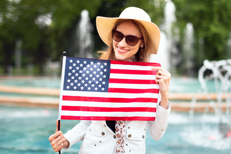 Young patriot woman in hat smilig and stretching USA flag in park and celebrating Indendence day, 4th of July
