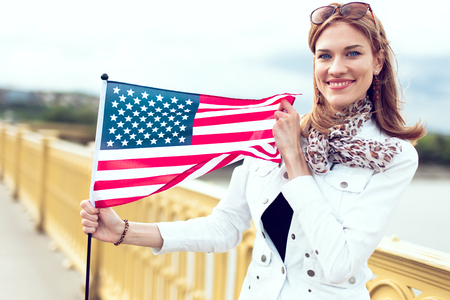 Happy young fashionable urban woman with toothy smile stretching USA flag
