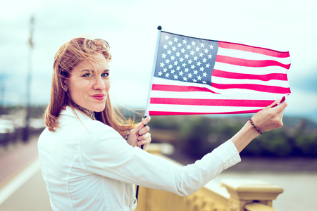 Young patriot modern woman with toothy smile stretching USA flag