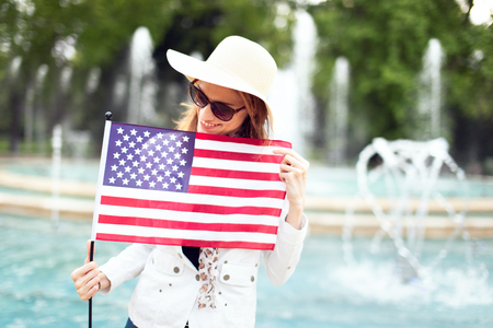 Young woman in hat looking down USA flag in park, Indendence day, 4th of July