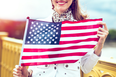 Happy young patriot urban woman with toothy smile stretching USA flag concept in sunset Фото со стока