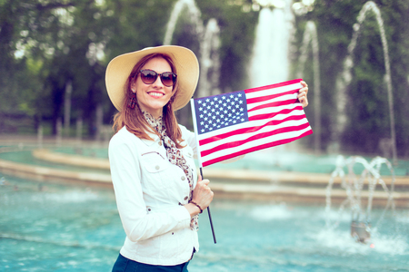 Happy young patriot woman in hat stretching USA flag in park, Independence Day, Fourth of July Фото со стока