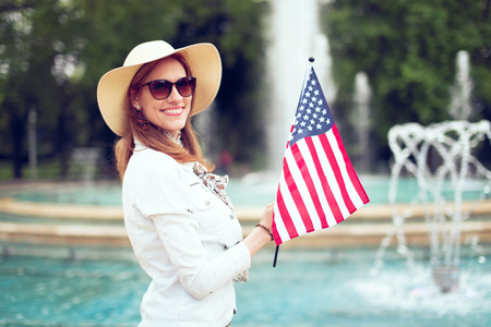 Young patriot woman in hat holding USA flag in park at fountain, Independence day, 4th of July
