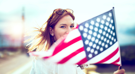 Happy young patriot modern urban woman holding USA flag portrait, depth of field, selective focus