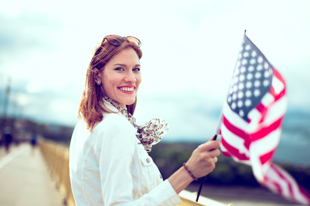 Happy young patriot modern urban woman holding USA flag portrait, looking back