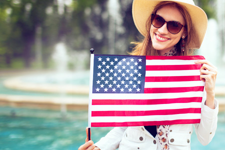 Happy young patriot woman in hat stretching USA flag in park, 4th of July, Independence day