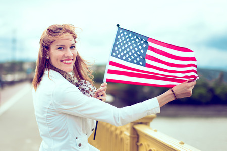Happy young patriot urban woman with toothy smile showing stretched USA flag Фото со стока